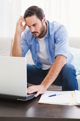 Worried man sitting at table using laptop to pay his bills