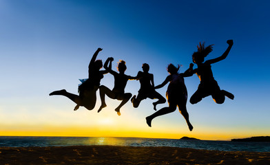 Teens jumping on the beach at sunset