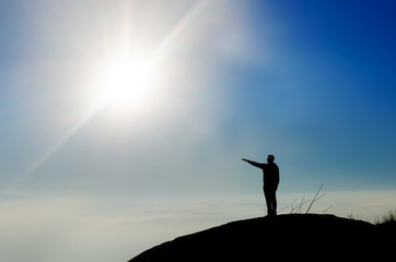 Silhouette of a champion on mountain top pointing