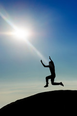 Man jumping on mountain peak at bright sky.