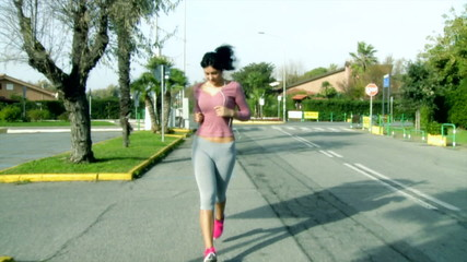 Beautiful young woman jogging on street listening music happy