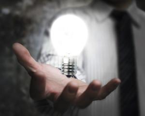 businessman hand holding brightly light bulb illuminated dark