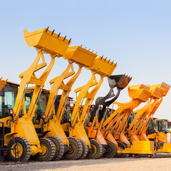 The row of heavy construction excavator machine  against blue sk