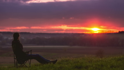 The man sitting by picturesque sunset, time lapse
