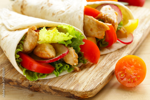 Keuken foto achterwand Snack chicken burrito with radishes, sweet peppers and salad