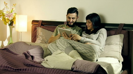Happy couple in bed having good time with tablet