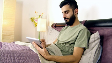Man in bed enjoying tablet in the morning at home