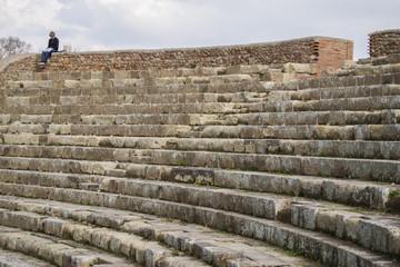 Uomo che legge seduto in un teatro di epoca romana