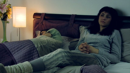 Sad woman in bed with husband feeling depressed