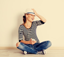 Vintage portrait of singing girl sitting at empty wall at home