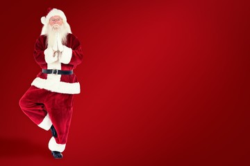 Composite image of father christmas doing some yoga
