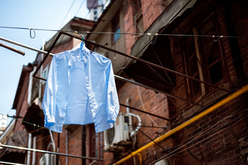 Blue shirt hanging on a washing line in the old town of Shanghai