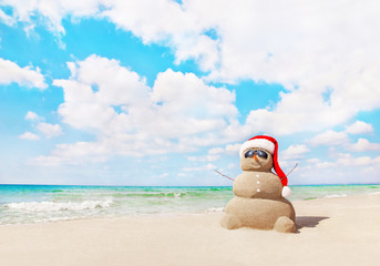 Sandy snowman in santa hat on sea beach. New Years and Christmas