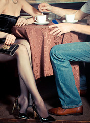 Male and female legs during a date in the restaurant.