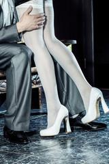 girl in white stockings seduces man indoors.
