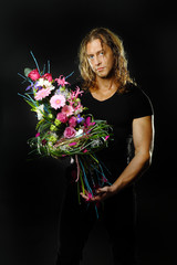 male fitness model shirtless holding a bouquet of flowers.