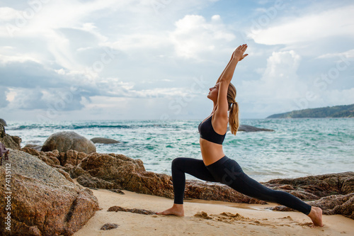 women doing yoga with the ocean behind - 74135112