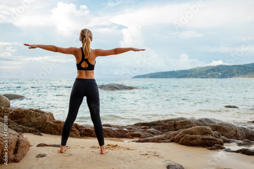 Tuinposter Gymnastiek women doing yoga with the ocean behind