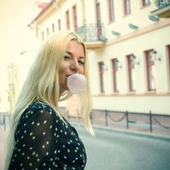 Trendy beautiful blond girl  Blow bubblegum.