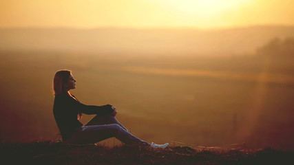 The young woman sit and dream on the top of the hill