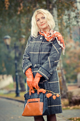 Beautiful mature blonde in checkered coat posing in the park.