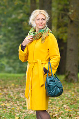 trendy Beautiful senior woman in a yellow coat walks in the park