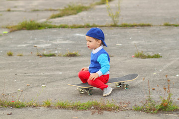 little boy having fun with skateboard outdoors.