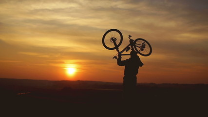 The biker by sunset background on the top of the hill