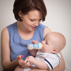 Young Mother Feeding Her Baby Boy With A Milk Bottle
