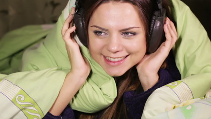 Girl with headphones smile bed home