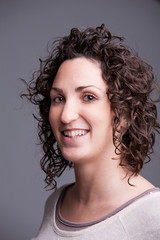 foreground portrait of a smiling curly haired woman