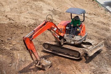 A worker drive the red excavator machine