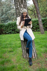 Happy young woman using tablet outdoors in a park.