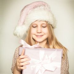 Young child girl dressed in Santa Claus hat with Christmas gift