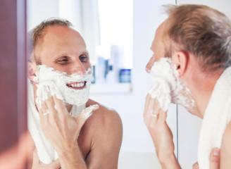 Shaving man near the bathroom mirror