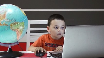 Child learning using laptop and globe earth