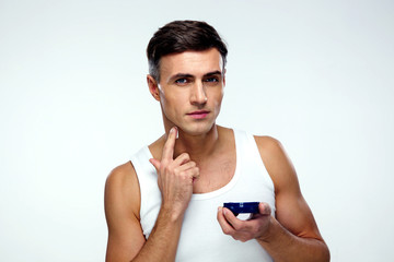 Man putting on cream lotion on face over gray background