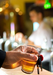 man holding car key and glass in the bar