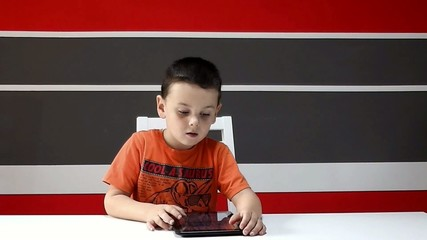 Kid sitting using tablet