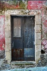 Vecchia porta con finestra in vetro e tenda ricamata