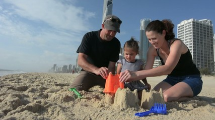 Family builds sand castle 01