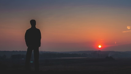 Man stands by sunset backgroundd
