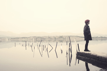 Woman in black standing on jetty in a lake