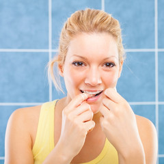 Young Woman flossing her teeth