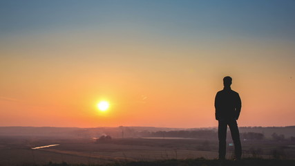 Man stands by sunset background, time lapse