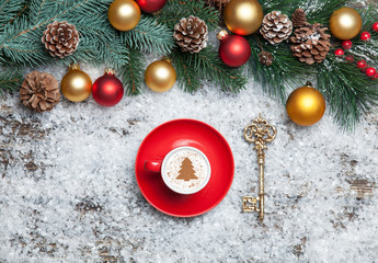 Cappuccino with christmas tree shape and key on artificial snow