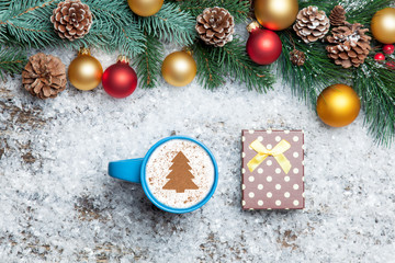 Cappuccino with christmas tree shape and gift box on artificial