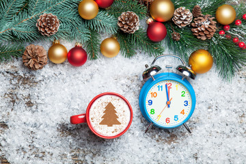 Cappuccino with christmas tree shape and clock on artificial sno