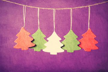 Five christmas tree toys hanging on jute thread.