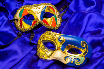 Two colorful Mardi Gras Masks on blue silk